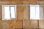 foto of glass-wool  - Inside wall heat isolation with mineral wool in wooden house building under construction - JPG