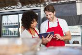image of apron  - Colleagues in red apron using tablet at the bakery - JPG