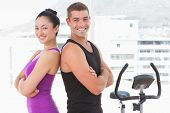 Fit couple smiling at camera with arms crossed in fitness studio poster