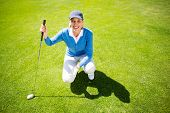 stock photo of ladies golf  - Smiling lady golfer kneeling on the putting green on a sunny day at the golf course - JPG