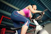 stock photo of slender legs  - Determined young woman working out at spinning class against fitness interface - JPG