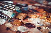 foto of paint palette  - Paintbrushes closeup artist palette and multicolor paint stains - JPG