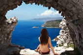 foto of topless  - girl with long hair sitting topless in a stone cave looking at the sea - JPG