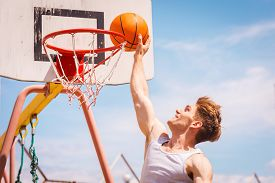 stock photo of slam  - Side view of young basketball player making slam dunk - JPG