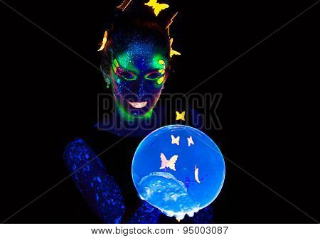 Portrait of woman holding blue luminous bubble