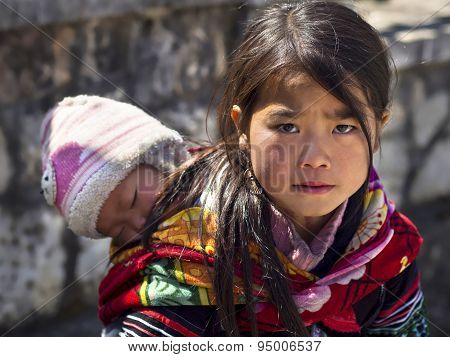 Unidentified Hmong Girl Carrying Baby In Sapa Town, Lao Cai Province, Vietnam
