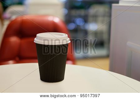 Paper Cup Of Hot Coffee With Red Chair Background