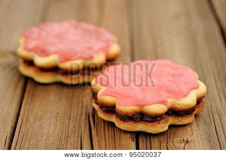 Two Round Sand Cakes Decorated With Pink Icing And Jam On Rustic Wooden Table Selective Focus
