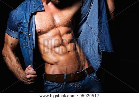 Muscular and sexy young man in jeans shirt with perfect fitness body