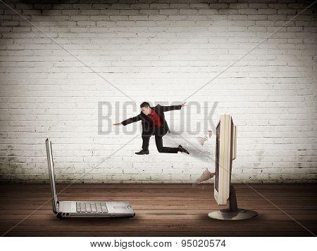 Business Man Jumping From Desktop Computer To Laptop