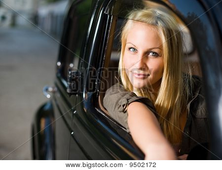 Beautiful young blond women posing in black vinateg car.