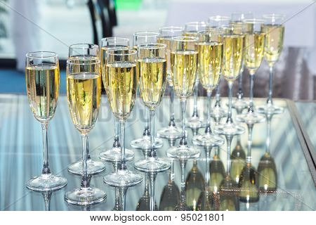 Elegant glasses with champagne standing in a row on serving table