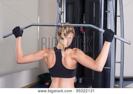 Strong fitness woman perfoming back exercise in gym. Power training. Workout