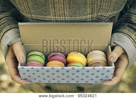Woman Holding Box With Colorful French Macaroons In Her Hands