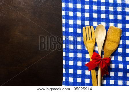 Wooden Table With Checked Tablecloth And Wooden Kitchen Utensils With Red Ribbon