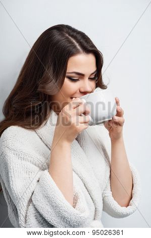 Pretty young girl is drinking hot tee