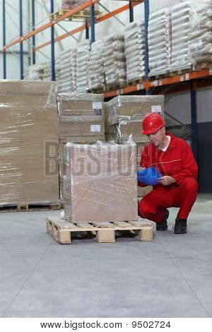 worker checking specification of goods in warehouse