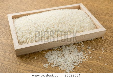Uncooked Jasmine Rice In Brown Wooden Tray