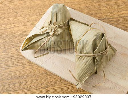 Two Zongzi Or Sticky Rice Dumpling On Wooden Board