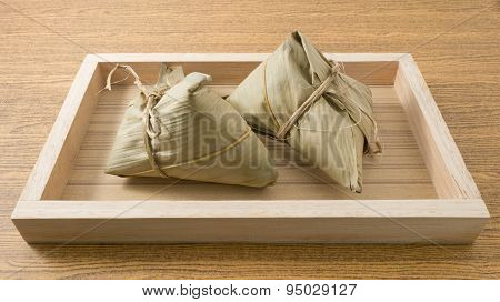 Two Zongzi Or Sticky Rice Dumpling On Wooden Tray