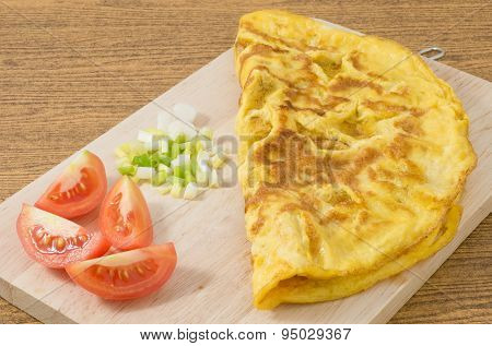Thai Omelette With Tomatoes And Scallion On Cutting Board