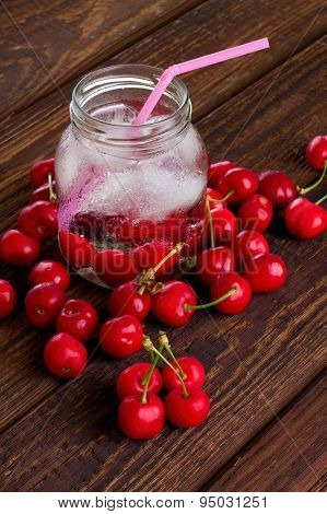 Pink Straw In Jar Among Heap Of Cherries