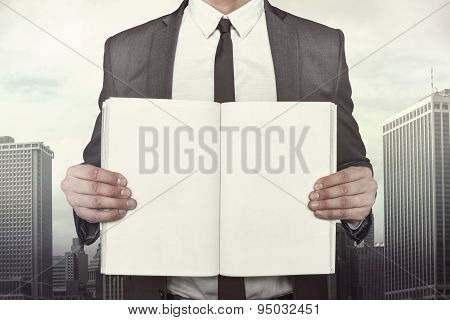 Businessman holding empty book front of him