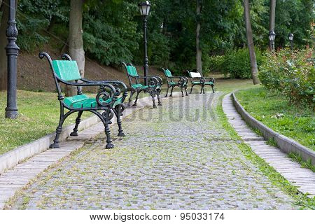 Park Walkway Of Paving Stones And Benches.