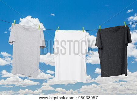 Close Up Of Three T-shirts On The Rope (grey, White And Dark Grey). Cloudy Sky Background.