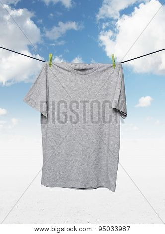 Close Up Of A Grey T-shirts On The Rope. Cloudy Sky Background.