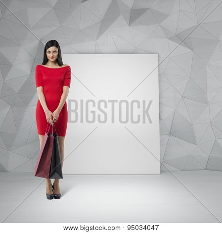 Beautiful Brunette Woman In A Red Dress Is Holding Fancy Shopping Bags. Contemporary Wall And An Emp