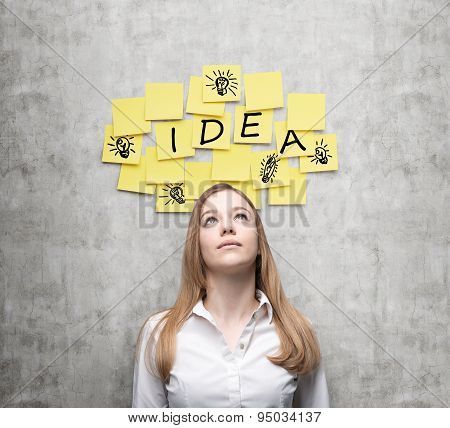 Young Business Lady Is Looking For New Business Ideas. Yellow Stickers With The Word ' Idea' And Ske