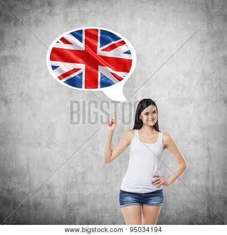 Brunette Lady Is Pointing Out The Thought Bubble With Great Britain Flag Inside. Concrete Background