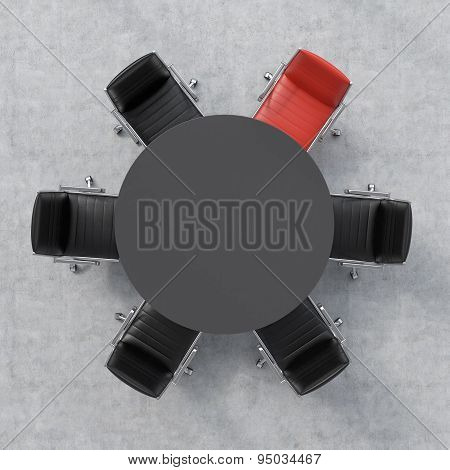 Top View Of A Conference Room. A Black Round Table And Six Chairs Around, One Of Them Is Red. Office