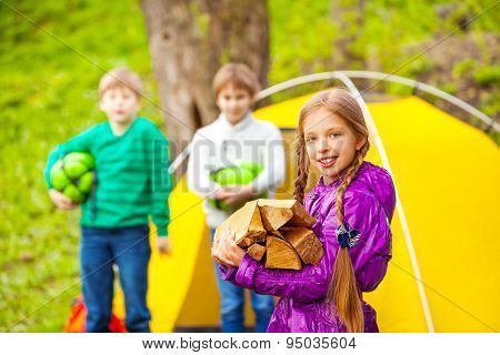 Girl holding the wood for bonfire with other kids