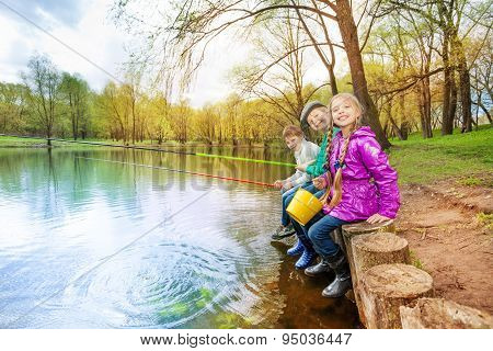 Kids sitting near pond holding fishing tackles