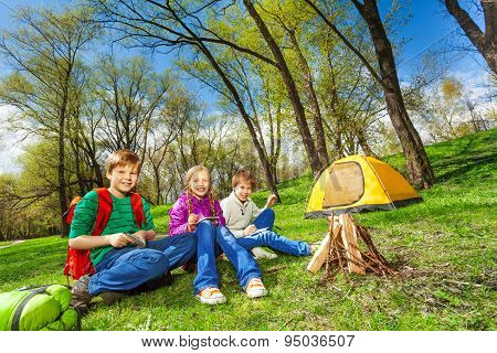 Happy children rest together near wooden bonfire