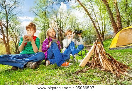 Three children resting near the wooden bonfire