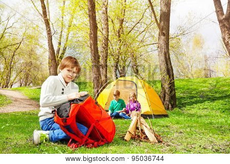 Boy packing the things into red rucksack in camp