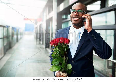 Happy Businessman With Flowers Calling On Phone