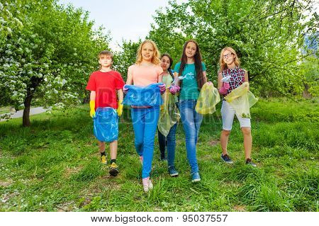 Happy teenagers wear gloves and carry garbage bags
