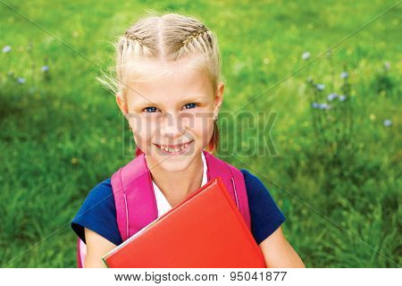 Portrait Of A Cute Schoolgirl With A School Bag And Textbooks. The Child Looks Into The Camera.