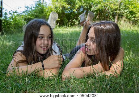 Front View Of Young Girls Laying On The Grass