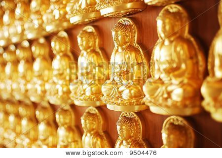 Many Of Golden Buddha Statue On Wooden Wall In Chinese Temple