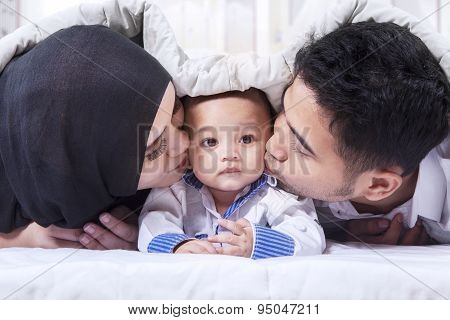 Beautiful Family Under A Blanket On Bed