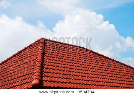 Techo de Grunge rojo con cielo azul nublado