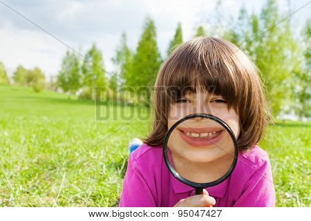 Funny boy smiles through magnifier, lays on grass
