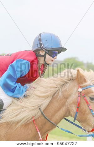 Young Girl Wearing Sun Glasses Riding A Pony