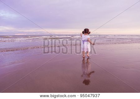 Cute Child Walking Along A Beach On Sunset