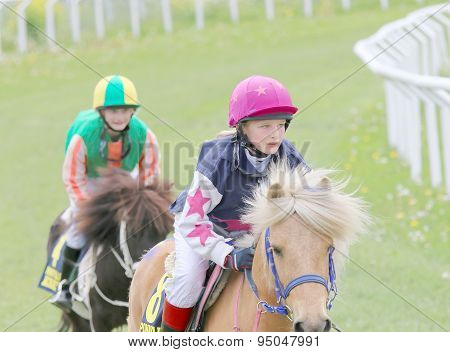 Young Girl And Young Boy  Sitting On Ponys
